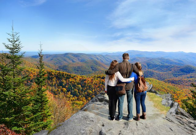 Family hiking in autumn mountains and watching views.