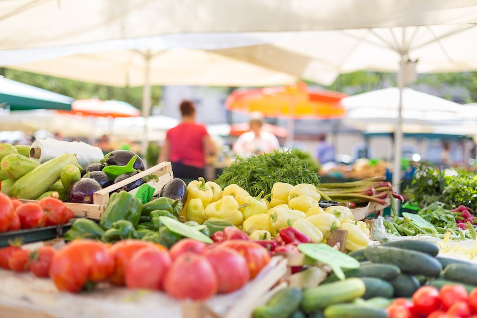 Vendor serving and chatting with customers at a farmers market.