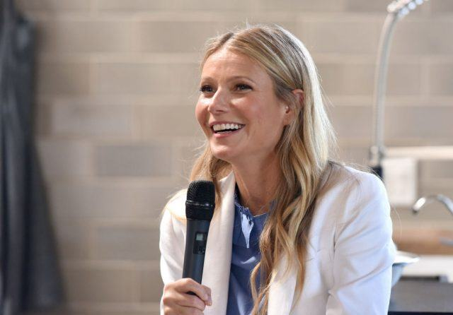 Gwyneth Paltrow smiles while holding a microphone.