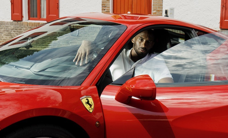 Kobe Bryant looks out of the open door of a red Ferrari he tested at the automaker's factory in Maranello, Italy.