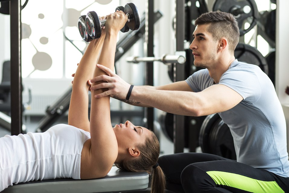 Fitness instructor exercising with his client at the gym