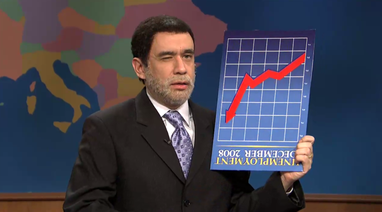 Fred Armisen wearing a suit and holding a chart