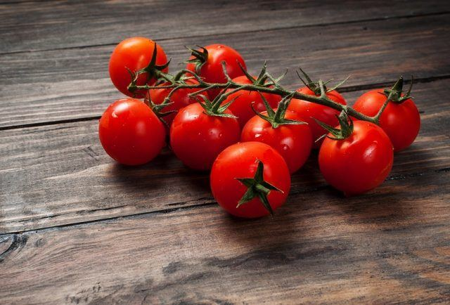 Cherry tomatoes on a wooden table.