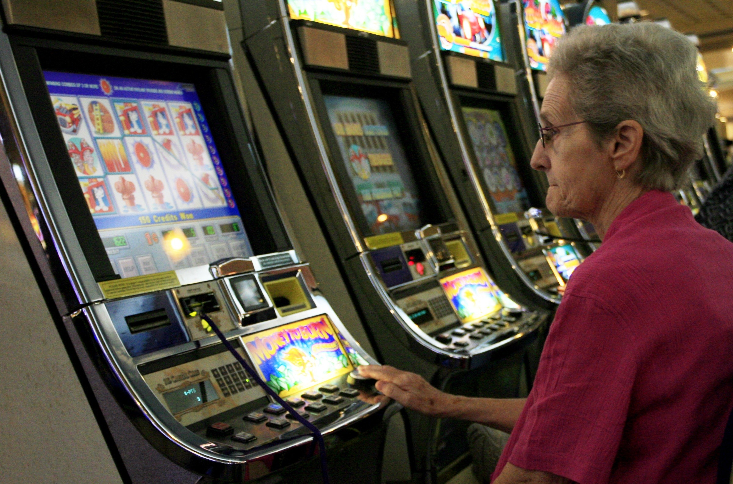 A tourist plays a slot machine while at a casino in Dover, Delaware