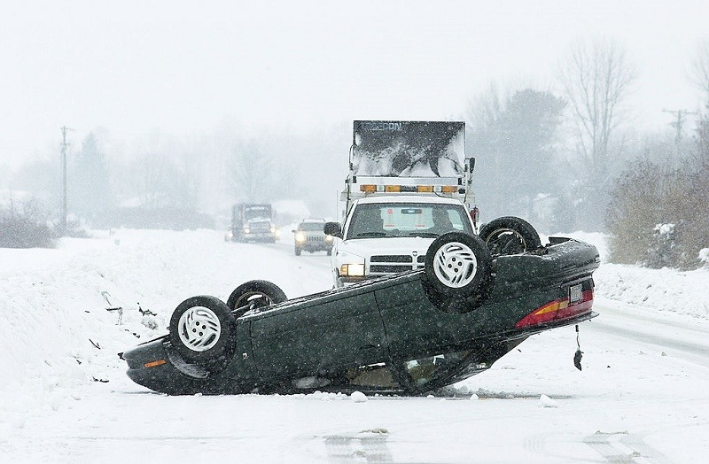 An overturned car sits on a snow-covered highway February 18, 2003 near Milford, Delaware. A State of Emergency was declared for the entire state after a record snowfall hit the three counties surrounding Milford.