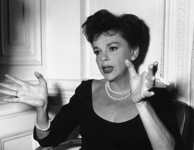 Judy Garland gestures with her hands while wearing a black dress and pearls.