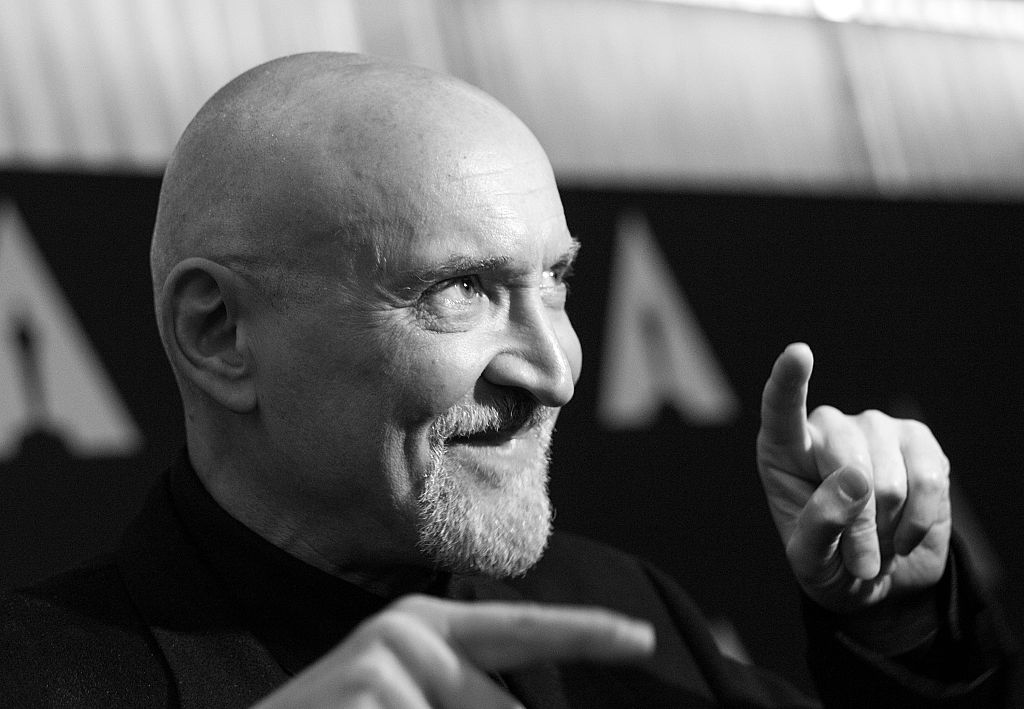 Frank Darabont in black and white, pointing both fingers in different directions and smiling