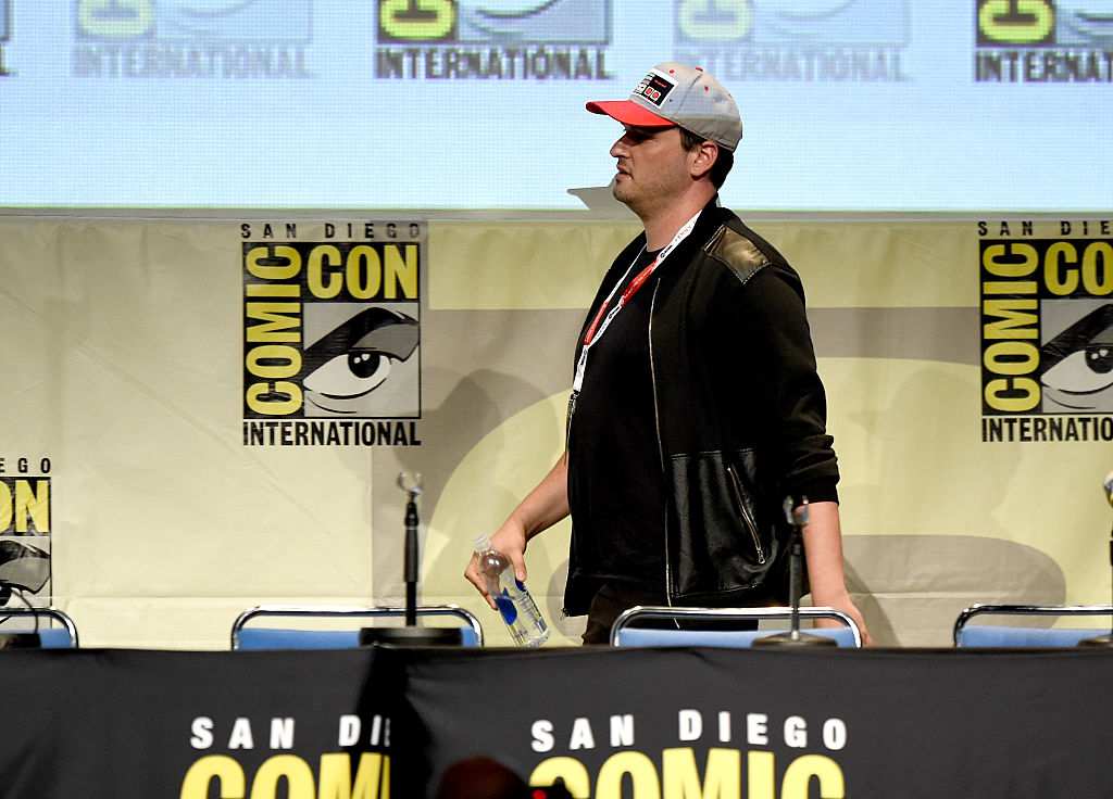 Josh Trank in a ballcap, walking on-stage at Comic-Con