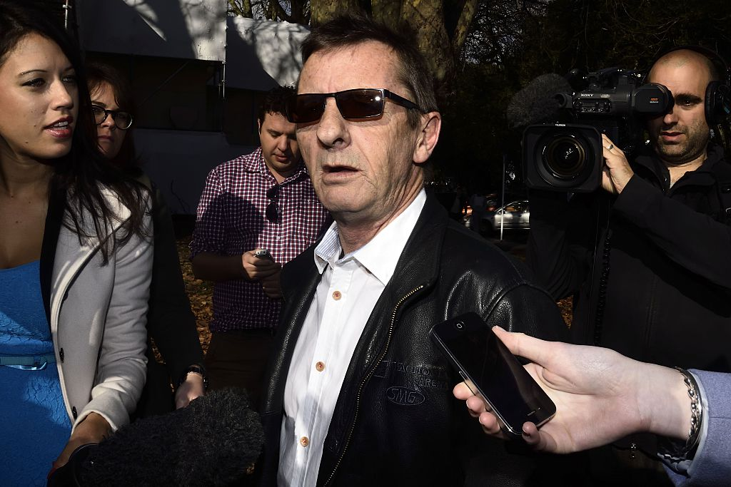 Phil Rudd wearing sunglasses and a suit, speaking into a collection of microphones