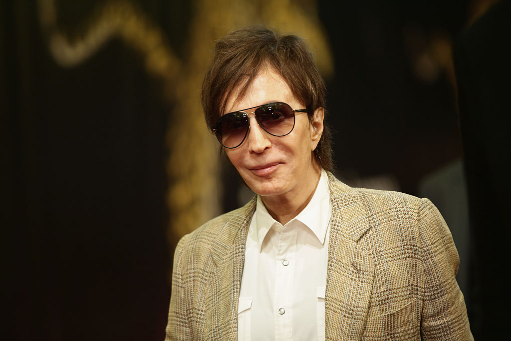 Michael Cimino wearing a tan jacket and sunglasses, smiling for the camera