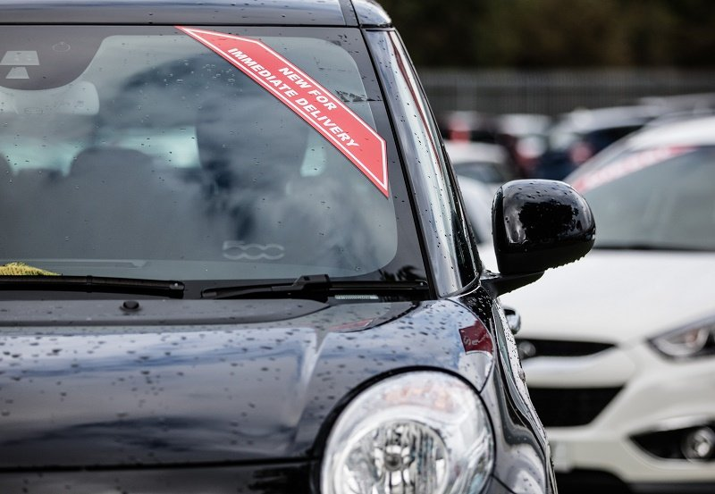 Unregistered cars are offered for sale on the forecourt of a car dealership