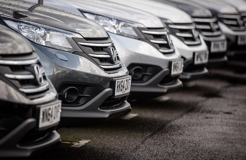 Hondas are lined up for sale on a lot