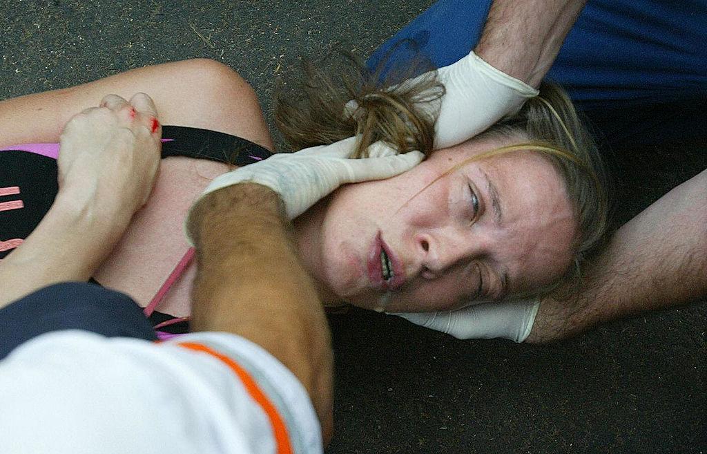 EMTs help a woman suffering a seizure