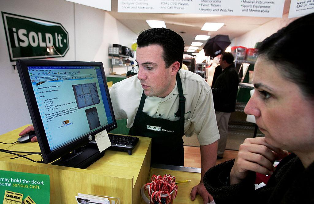 A retail manager assists an associate