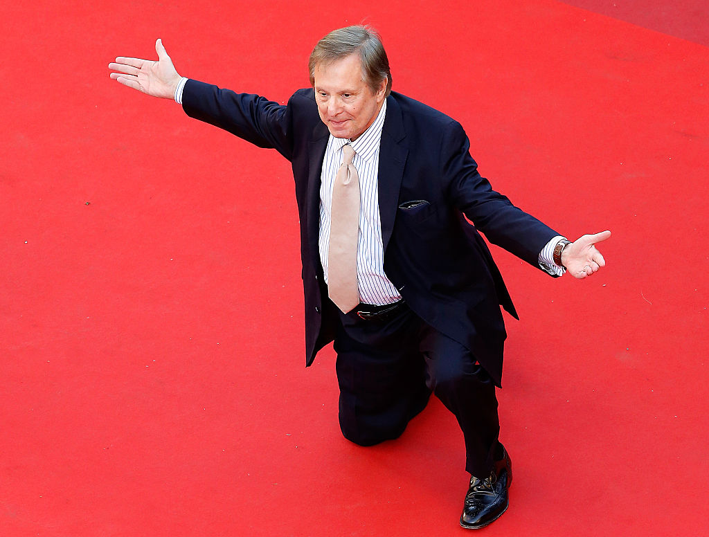William Friedkin down on one knee on the red carpet, with both arms extended out