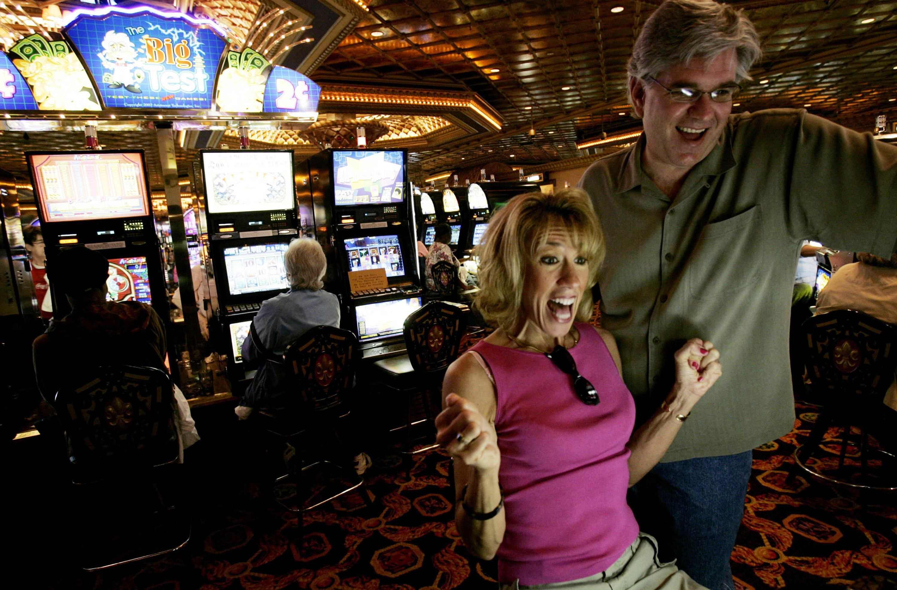 A couple celebrates winning after a couple of spins on the slot machines