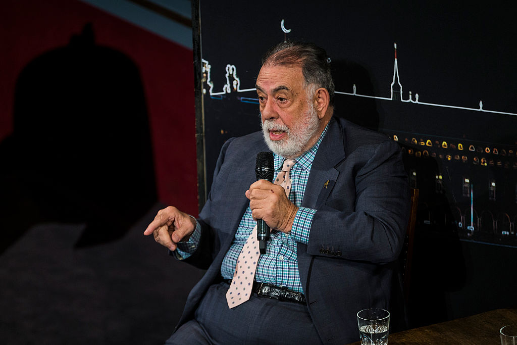 Francis Ford Coppola, sitting in a chair, speaking into a microphone, and pointing with his right hand