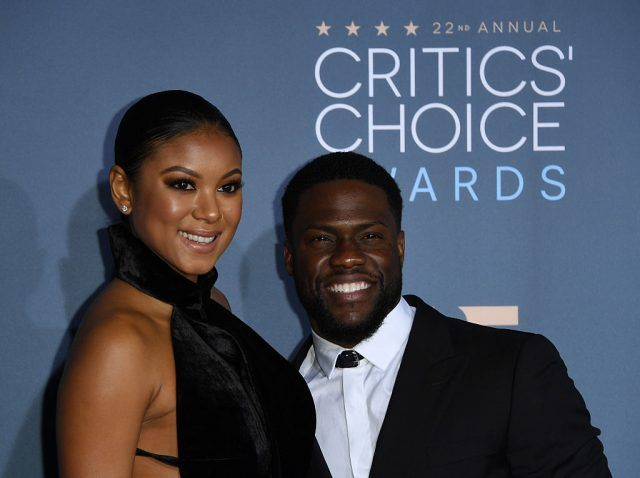 Enika Parrish and Kevin Hart, smiling together for the camera's on the red carpet.