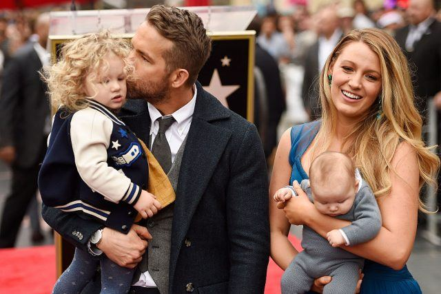 Blake Lively and Ryan Reynolds hold their daughters on the Hollywood Walk of Fame.