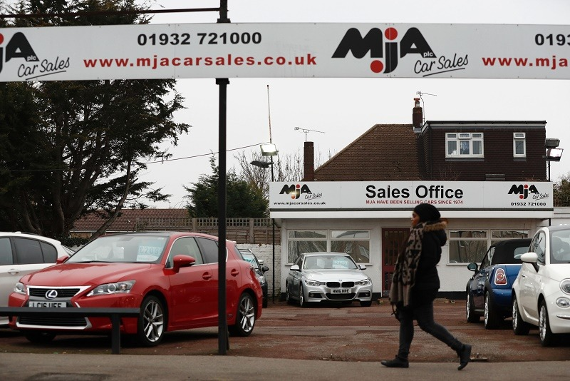 Second-hand cars sit on the forecourt of a used car lot