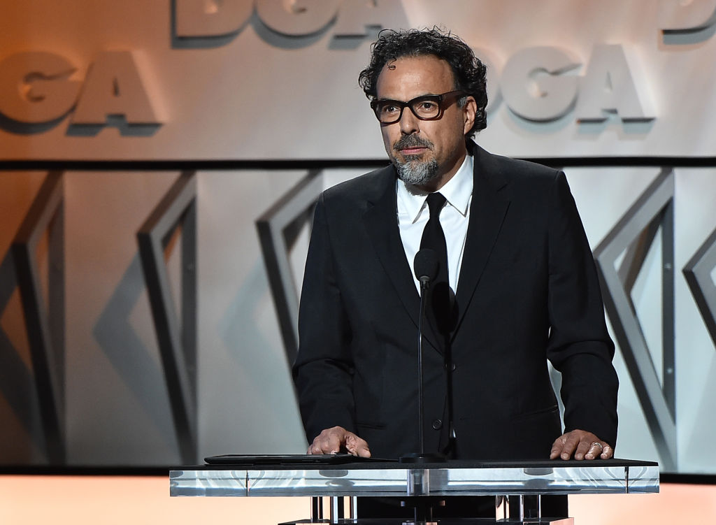 Alejandro Gonzalez Inarritu speaking at a podium, wearing a suit