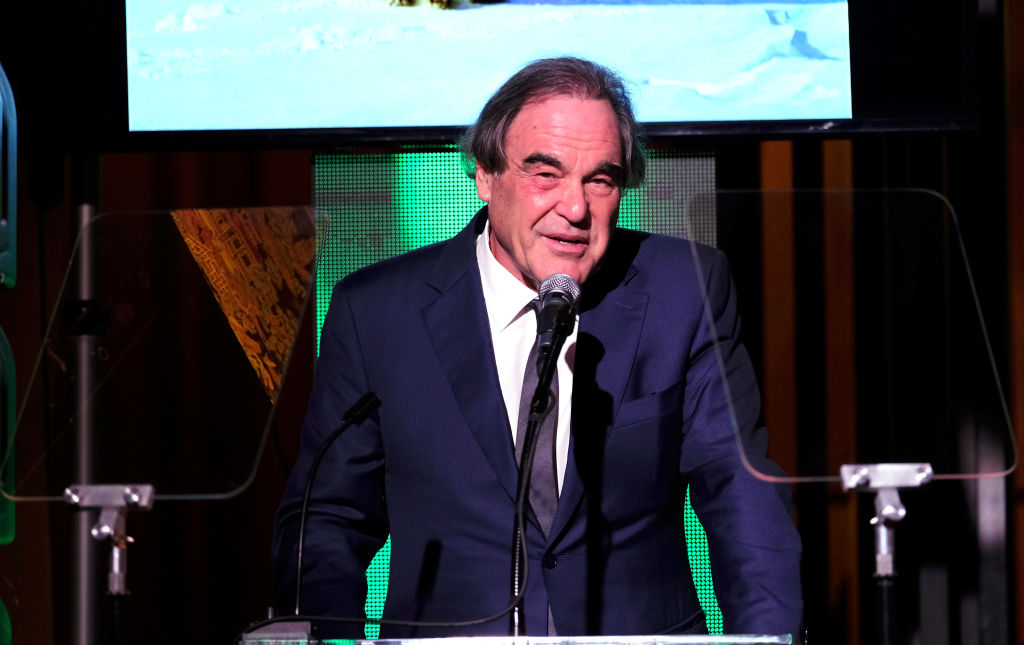 Oliver Stone in a suit, speaking at a podium