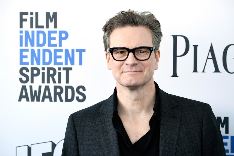 Colin Firth wears glasses and a black suit while posing on the carpet for the Film Independent Spirit awards