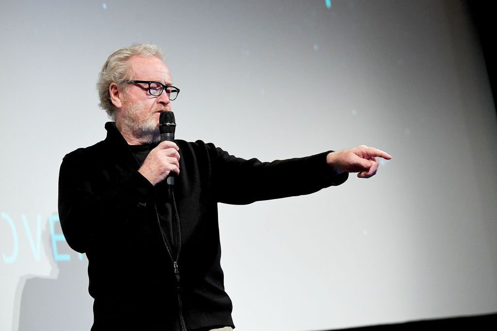 Ridley Scott wearing all black, speaking into a microphone, and pointing with his left hand