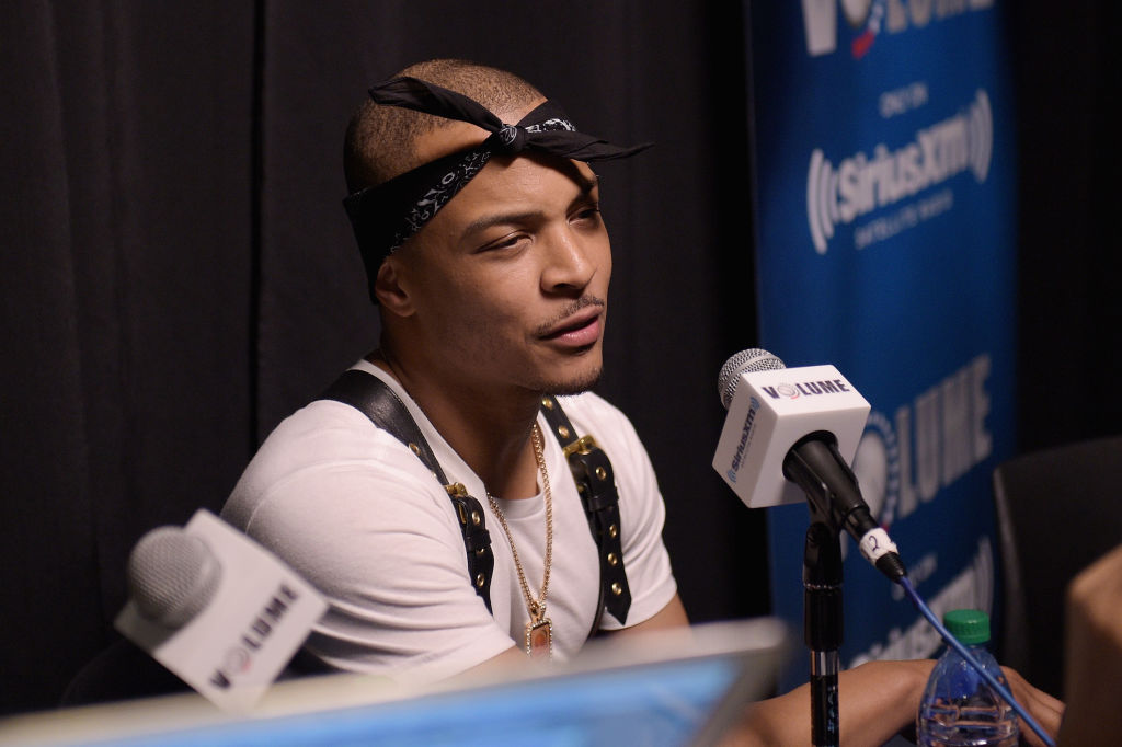 T.I. wearing a black bandana around his head, speaking into a microphone