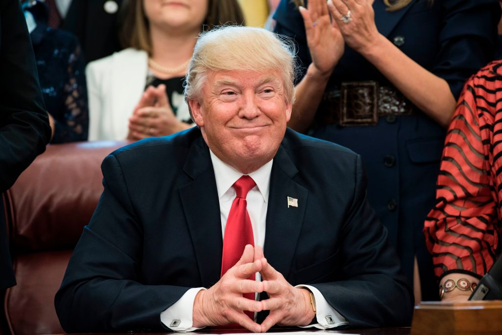 Donald Trump smiling, with his hands folded on a table