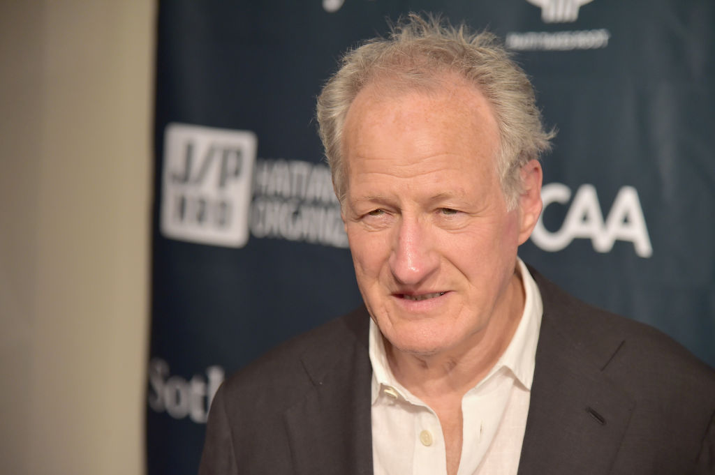 Michael Mann wearing a grey suit jacket and white collared shirt