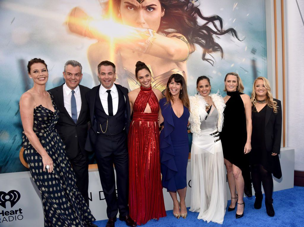 The cast of 'Wonder Woman' with their arms around one another in front of a poster for the film