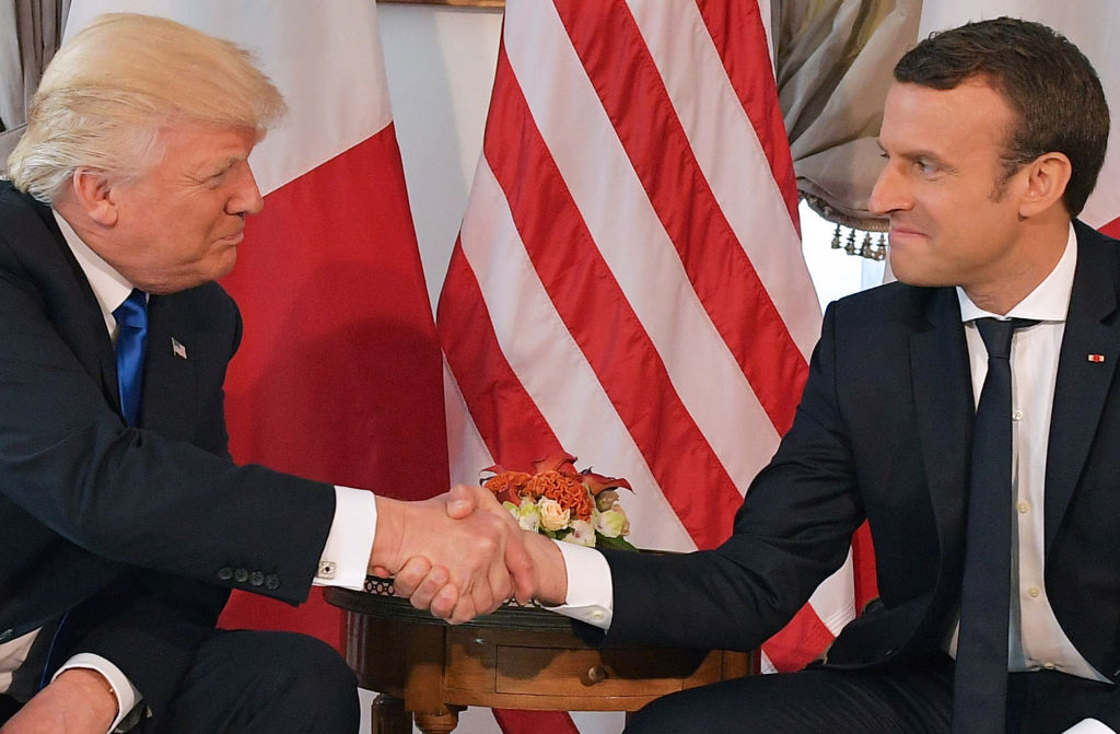 Donald Trump and French President Emmanuel Macron shake hands.