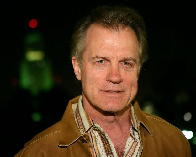 Stephen Collins in a tan jacket and collared shirt, smiling slightly for the camera.