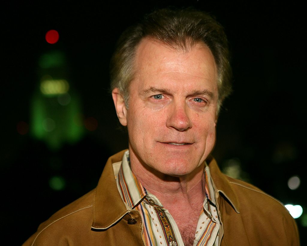 Stephen Collins in a tan jacket and collared shirt, smiling slightly for the camera