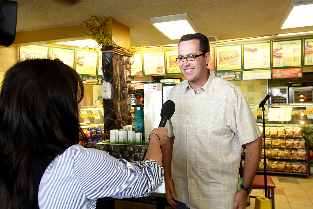 Jared Fogle smiling in a Subway, speaking into a microphone held by a reporter