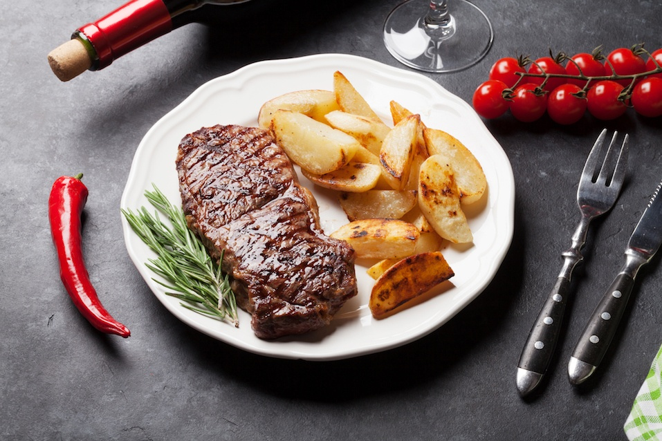 Grilled striploin steak with potato and red wine over stone table