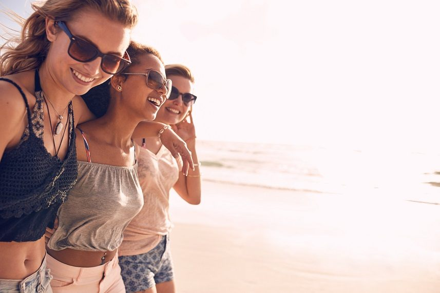 women strolling on a beach