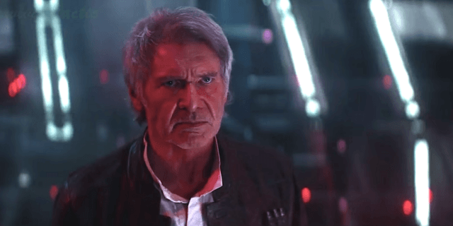 Han Solo cast in red light, looking defiantly on at his son offscreen.