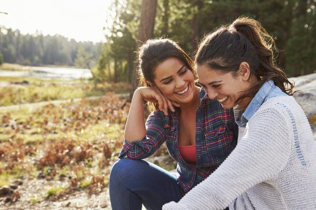 Two women laugh and talk in the countryside.