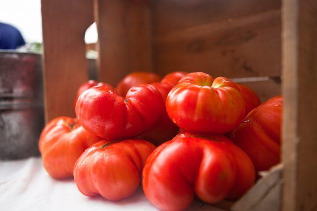 Tomatoes stacked next to a wooden crate.