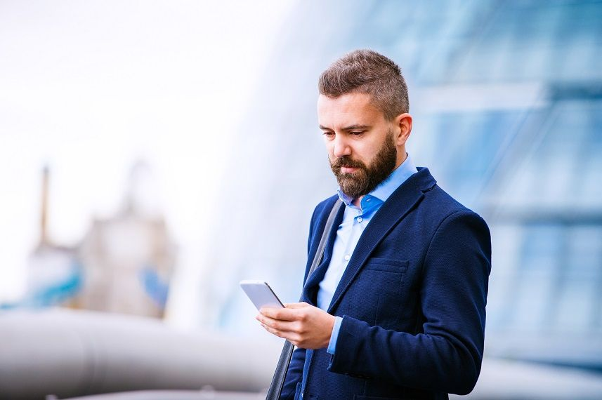 man in suit holding a smartphone