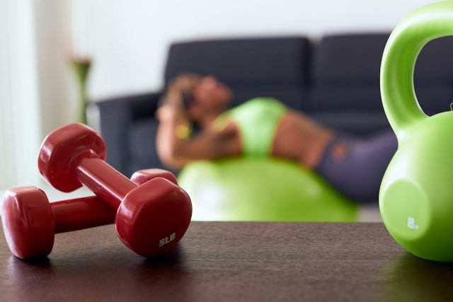 A woman works out in her living room.