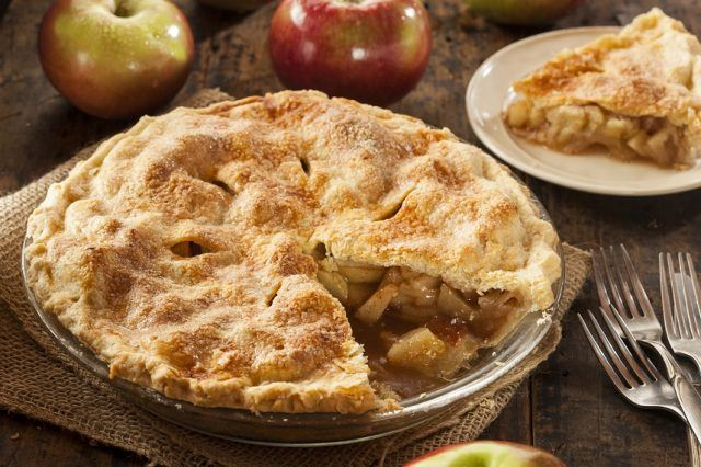 A homemade apple pie and forks on a wooden table.