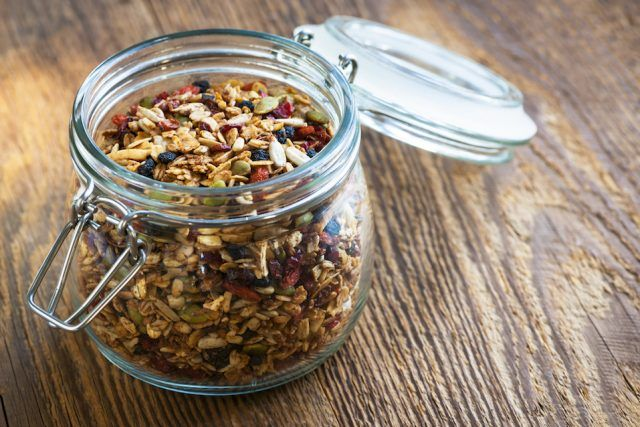 Homemade granola in open glass jar on rustic wooden background.
