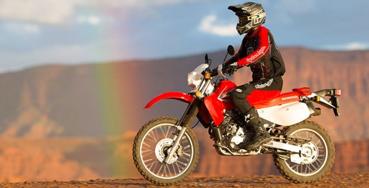 Photo of ride in helmet on Honda XR650L with rainbow in the sky
