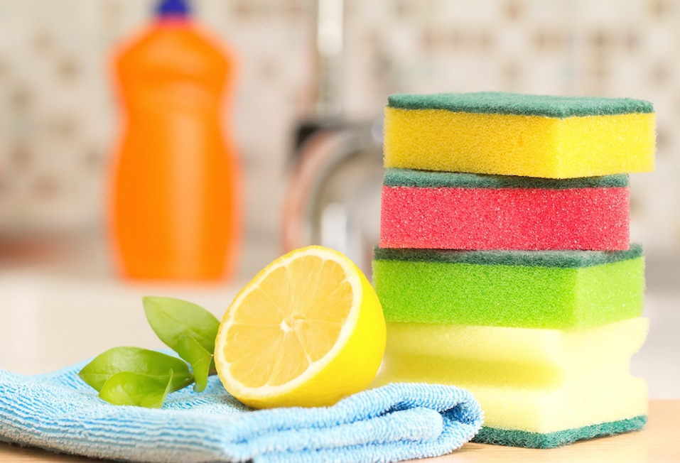 stack of sponges next to a lemon by a kitchen sink and dishwasher