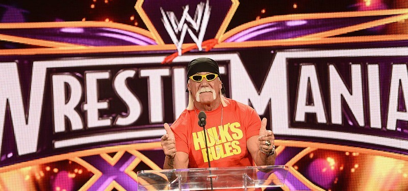 Hulk Hogan is giving two thumbs up at a podium in front of a Wrestlemania poster.