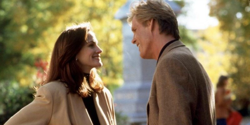Julia Roberts and Nick Notle look at each other smiling in a park in I Love Trouble.