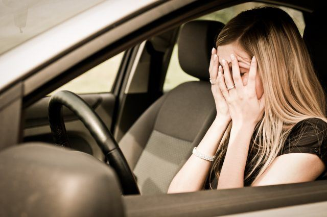 frustrated woman in car with head in hands